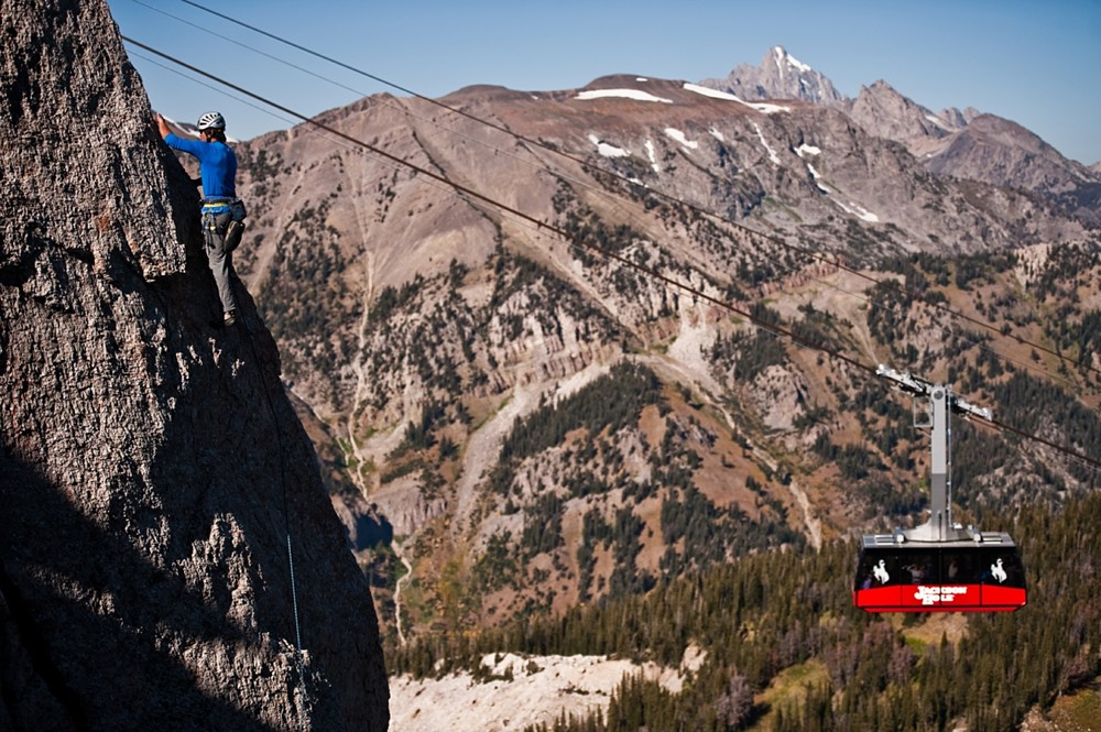 A rock climber makes his way up a face as a Jackson Hole tram car moves behind him