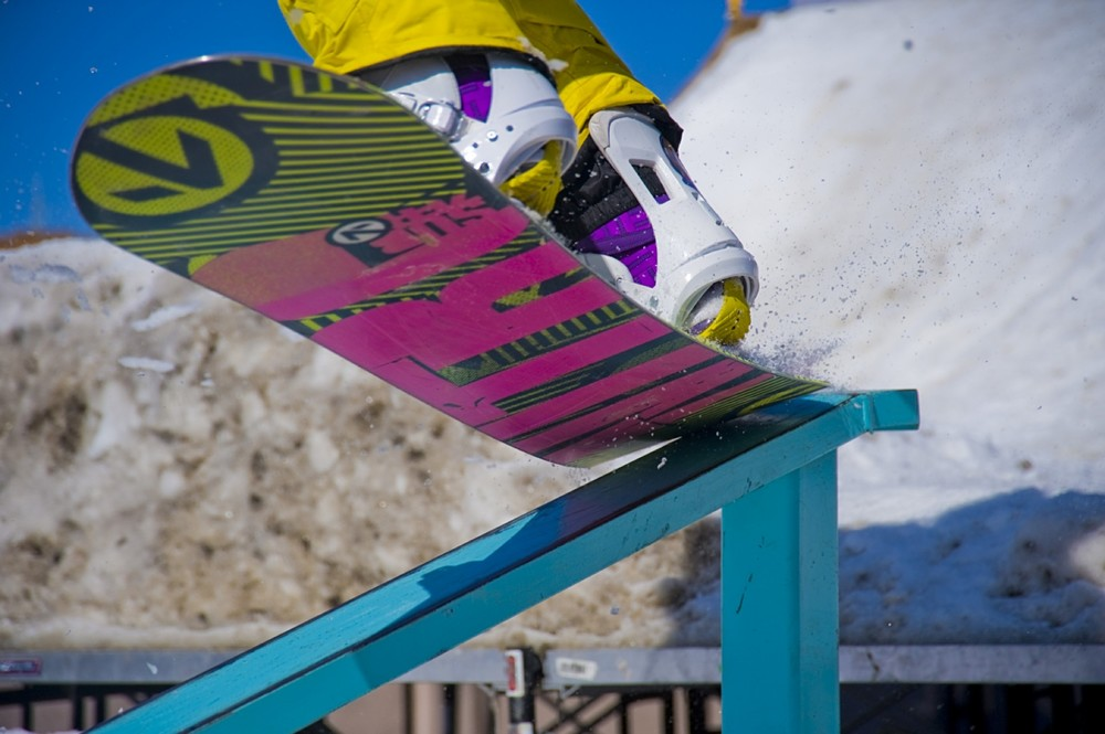 The bottom of a snowboard pictured as the rider begins a rail slide