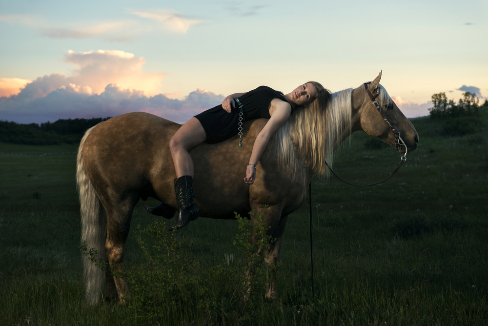 Creative portrait of a young woman laying on horse at sunset