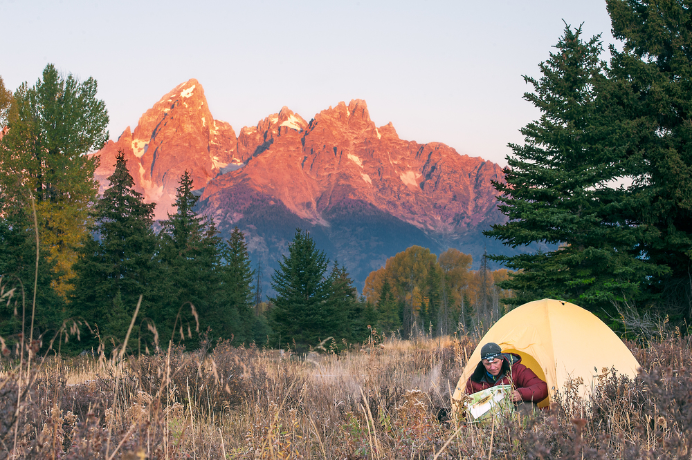 Sunrise lifestyle image of a man camping and making plans in Jackson, WY