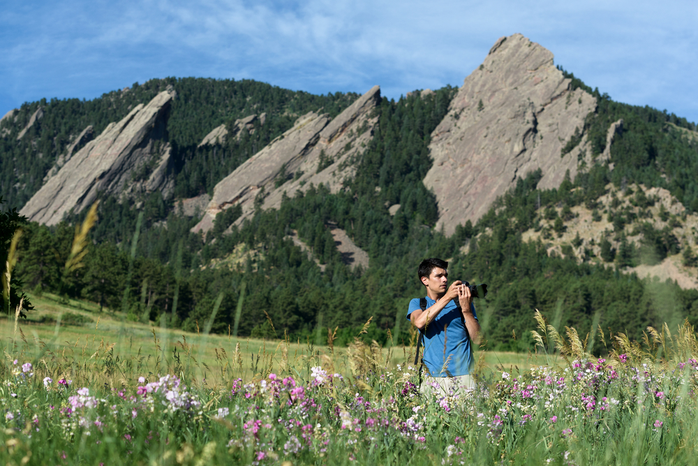 Active lifestyle advertising photo of a man taking photos and hiking near the Flat Irons outside of Boulder, CO.
