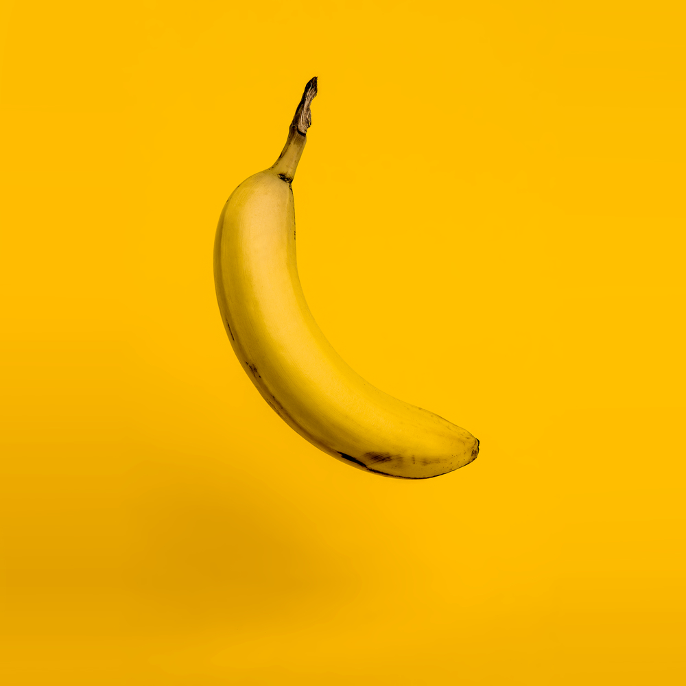 Still life editorial photo of a floating banana