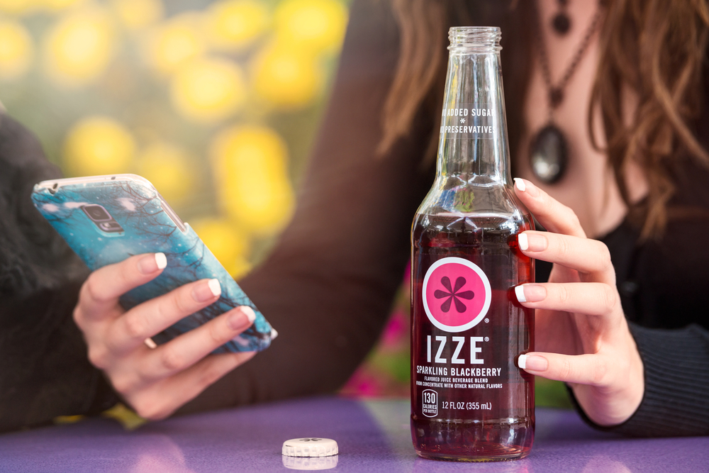 lifestyle product photo of Izze Blackberry in the summer