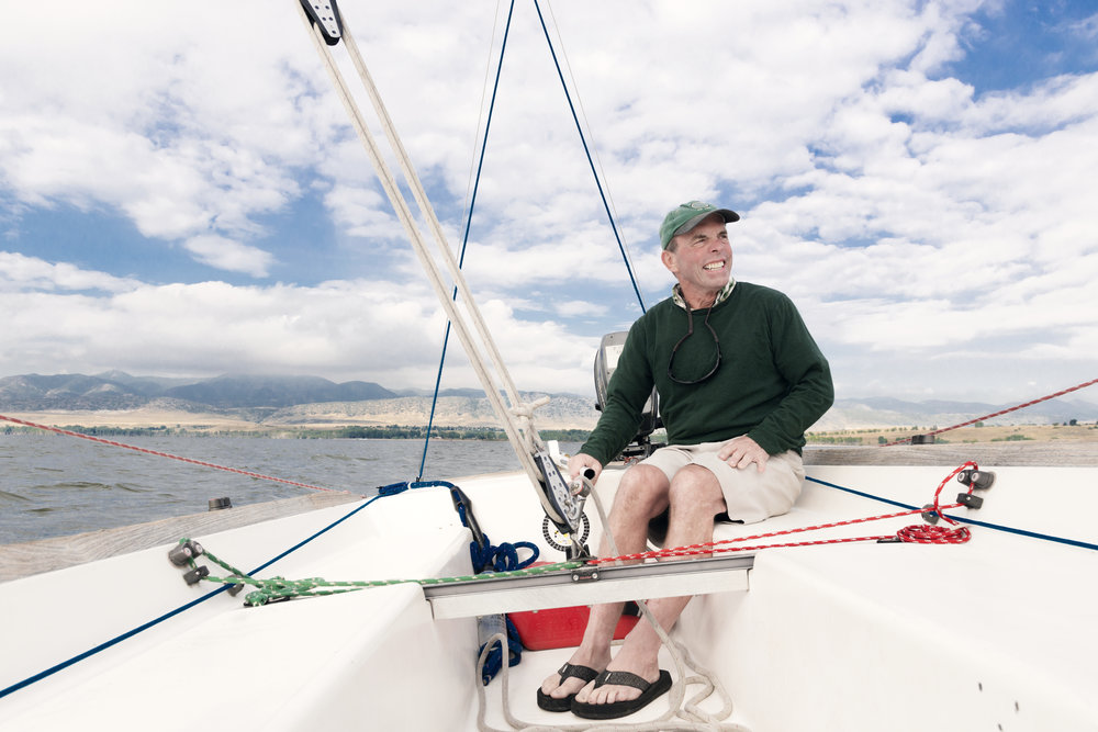A lifestyle photo of a man sailing a small boat on a resevoir south of Denver, CO