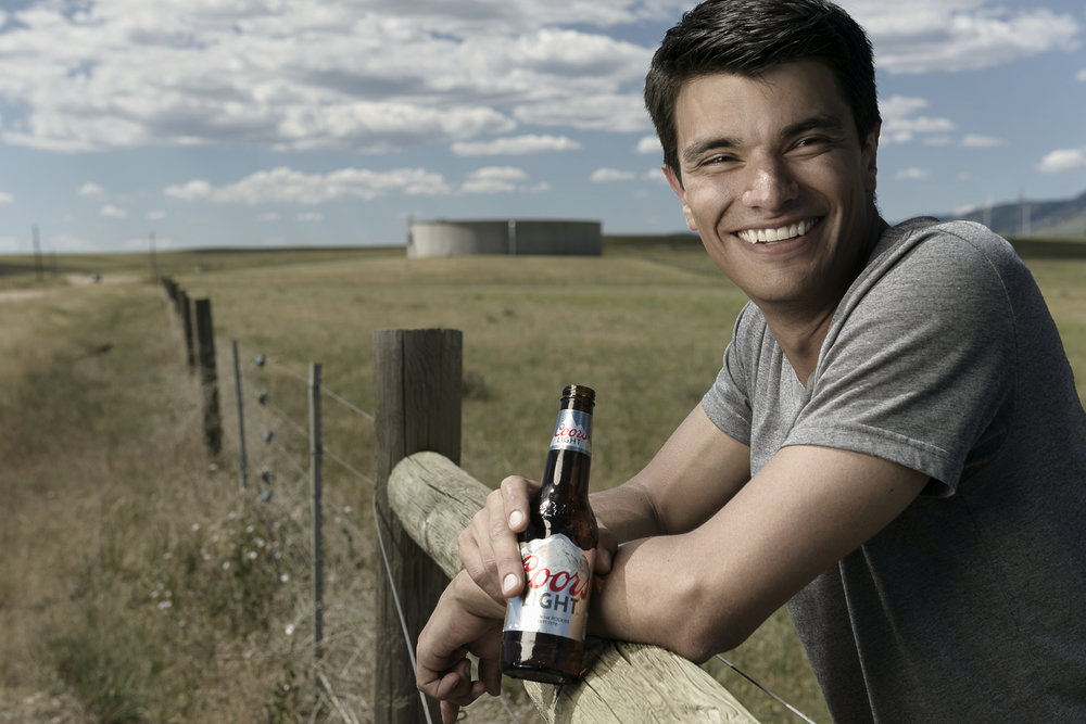 Location lifestyle advertising photo featuring male model and Coors Light