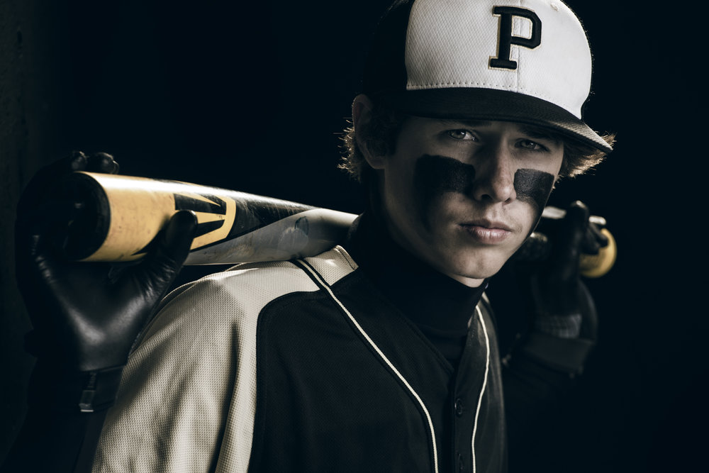 Close-in portait of a baseball player with an Easton bat
