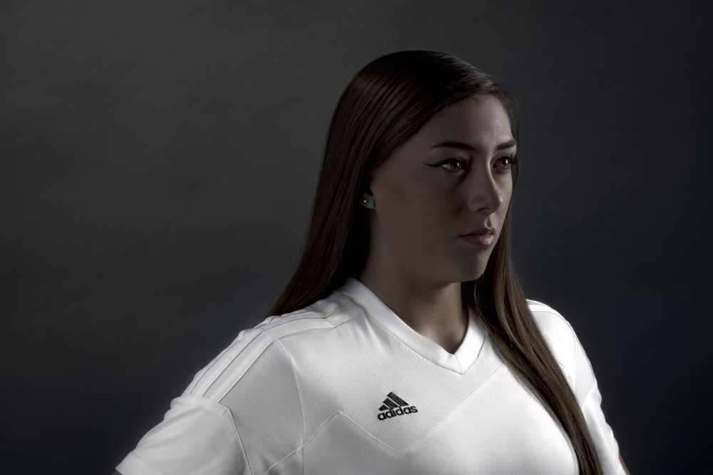 Female soccer player with white Adidas home kit jersey