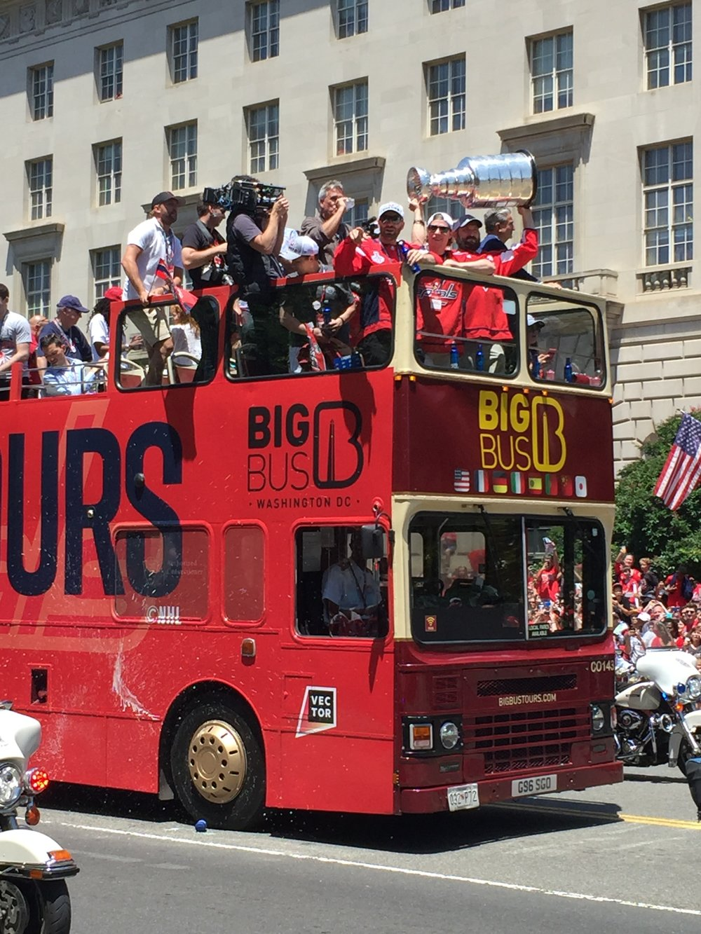 And finally, bringing up the rear, the save-the-best-for-last bus. Seems like we waited forever - you could see the tantalizing gleam of silver when it was still blocks away.  Atop the bus: (L to R) Capitals defenseman Brooks Orpik pointing at the crowd, beer in hand; center Nicklas Bäckström; and Captain & winger Alex Ovechkin holding Stanley above his head in iconic fashion. Caps owner Ted Leonsis is visible through the crook of Ovi's arm.