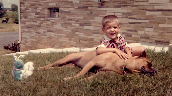 Patty R, taking a break after an exhausting romp with me in our backyard. Circa 1960 The picnic table in the distance (upper left)is in Poppa D's side yard.