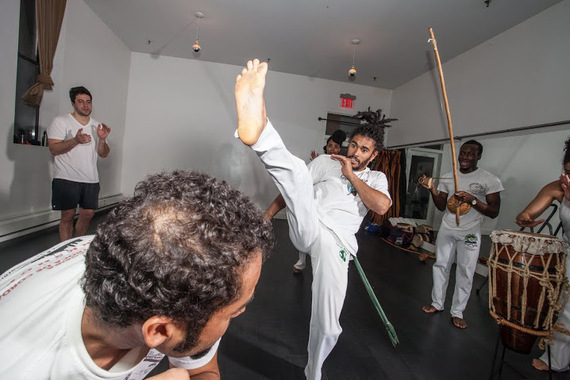 Students learn dozens of basic kicks, ducks and maneuvers which can be assembled in infinite variation, and practice them in a game of constant motion and surprise, as seen above with Pena kicking a Bênção and a student practicing a duck, or Esquiva, all done to the type of game determined by the music. (Photo by Ace Murray / Brooklyn Juice Photography.