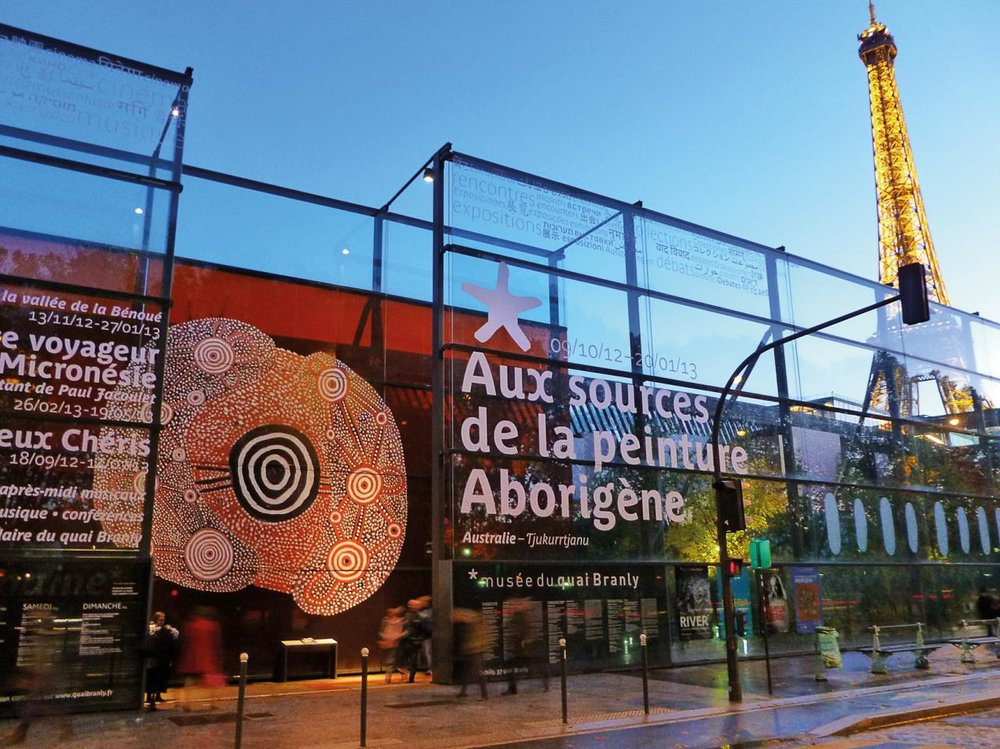 Entrance wall at Musée du qui Branly at night featuring John Tjakamarra's work  Man Dreaming , 1972 Photo courtesy of NGV International.
