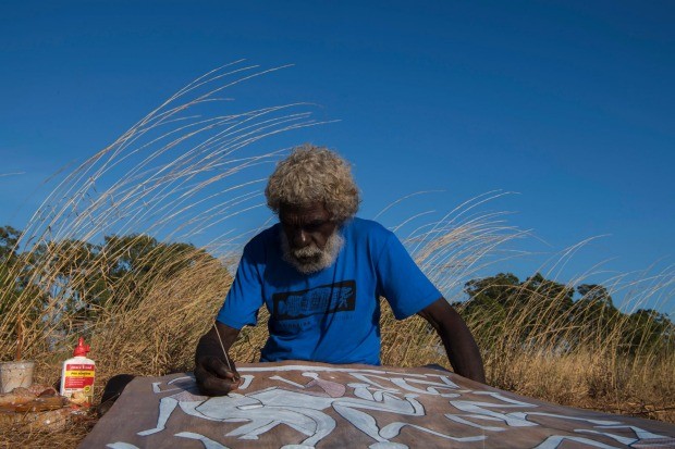 Australian contemporary Indigenous artist John Mawurndjul working on a bark painting at Maningrida.  Louise Kennerley
