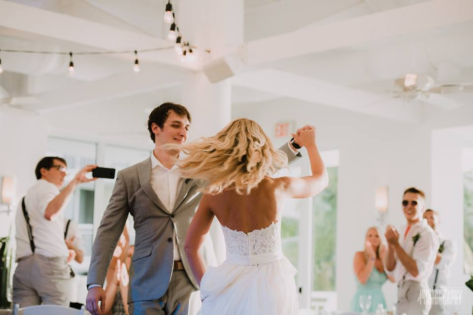 Couple swirling on the dance floor showing the bride's beach wave still intact after a full day of fun