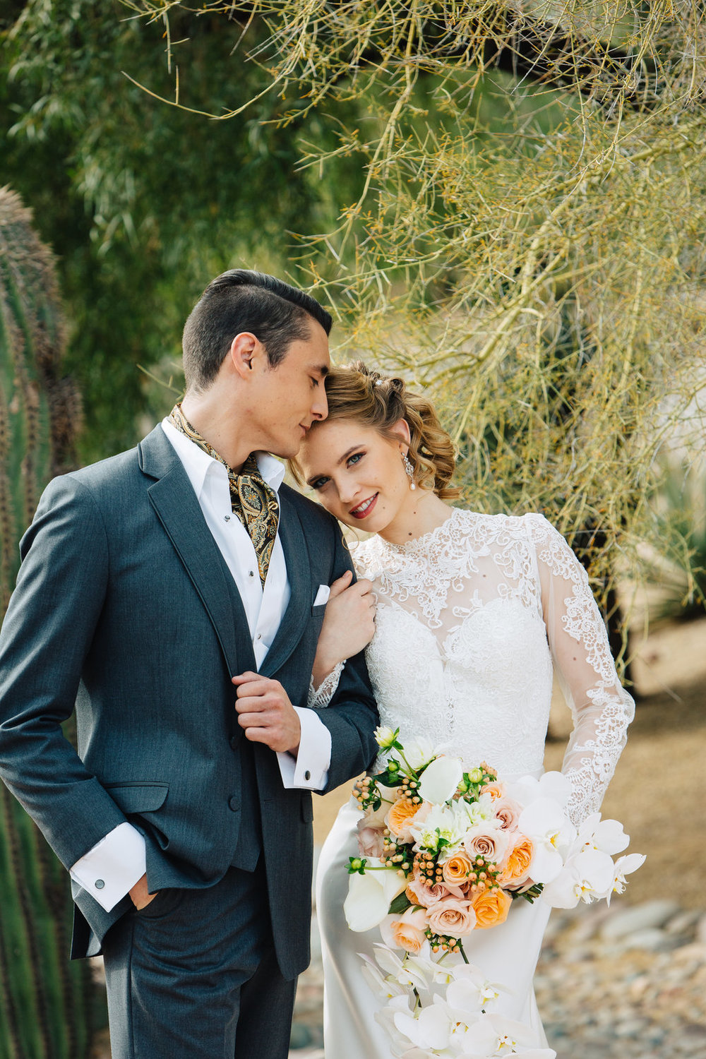 Bride, Groom, Phoenix Scottsdale Arizona Wedding Planner, Bridal gown, lace bridal gown, sleeved bridal gown, Groom attire, grey suite, southwest, ascot, groomsmen attire, Orchids, blush, peach, southwest, elegant, flowers, roses, rustic, western, bridal bouquet