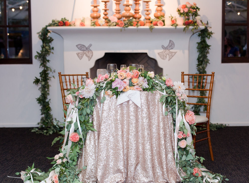 peach and mint wedding, blush and green wedding, Arizona Phoenix Scottsdale wedding planner, peach blush wedding flowers, sweetheart table, greenery with peach pink blush flowers, gold sequin linen, fireplace mantle decor, wooden candelabras, fireplace mantle greenery, desert wedding