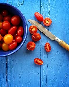 freshly-sliced-organic-cherry-tomatoes-on-blue-wooden-background.jpg