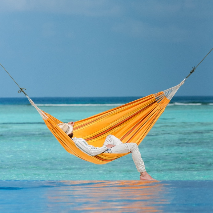 Young man retired early and now relaxes in a hammock watching the waves at the beach.