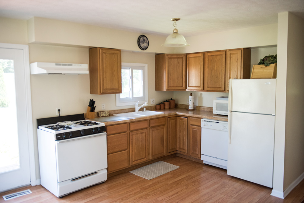 Main kitchen area with gas stove, refrigerator and dish washer.