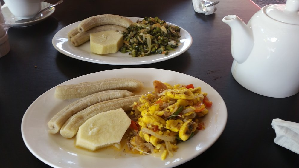 ackee and saltfish, with plantains at front and calaloo and plantains at the back