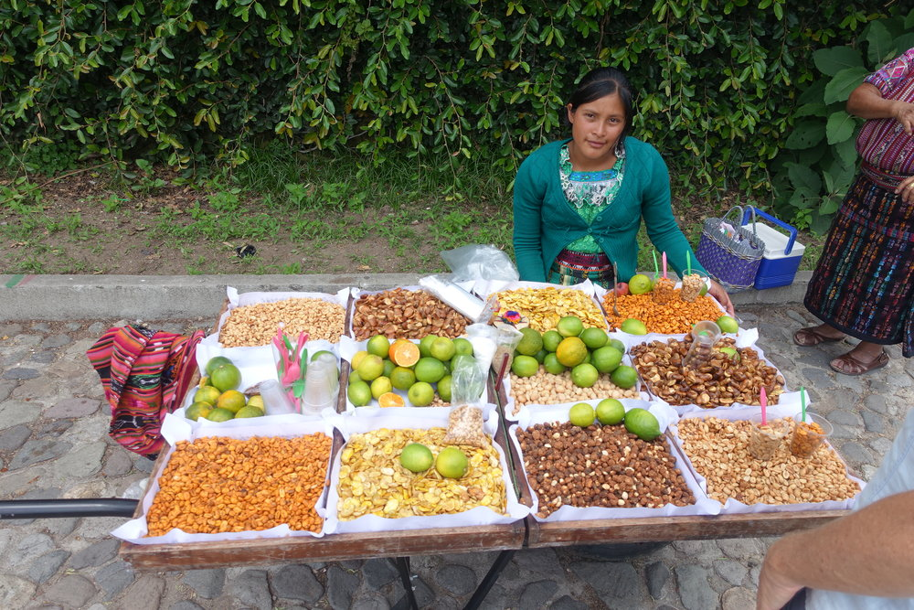 young woman selling nuts and citrus in pana
