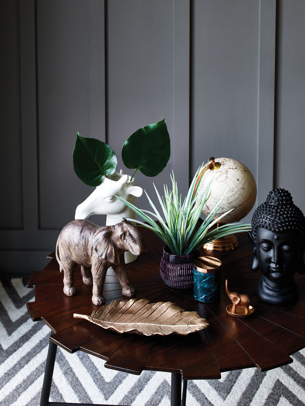 Elephant ornament - £15, Giraffe vase - £12, Copper globe - £15, Purple potted grass - £8, Marble print candle - £4, Buddha ornament - £12, Copper leaf plate - £12, Starburst coffee table - £79, Homemaker grey chevron rug - £60.