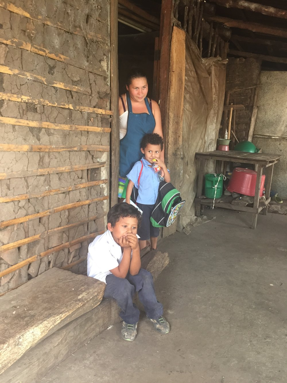 A mother with her two boys.  They are in line for a toilet to be shared with her sister's family, and a home when funding comes through.