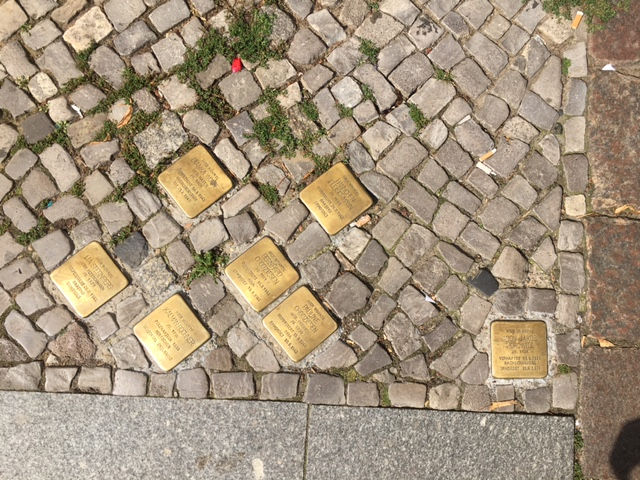 Plaques in the sidewalk commemorating the deportation of those who lived here.