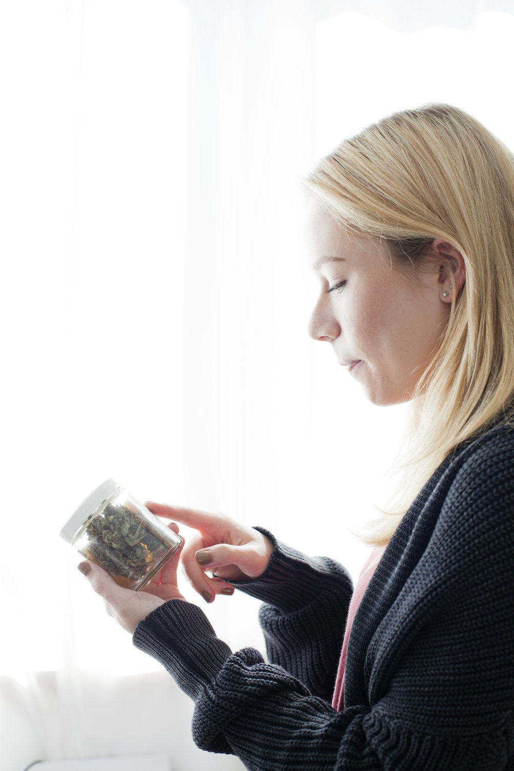 © Kristen Angelo Young woman reading label on cannabis jar