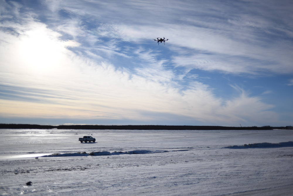 Truck driving on the frozen Kuskokwim River with Hexacopter in foreground