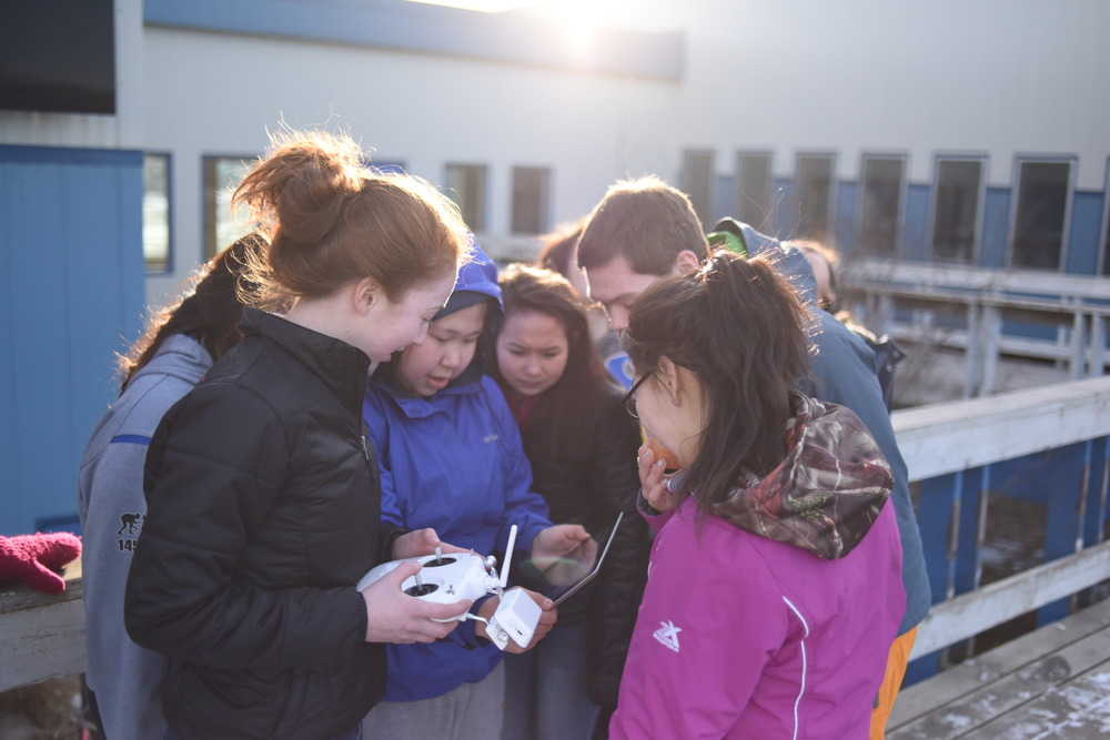Students view the Ipad for a first person view of a what a Phantom quadcopter above their school is seeing.
