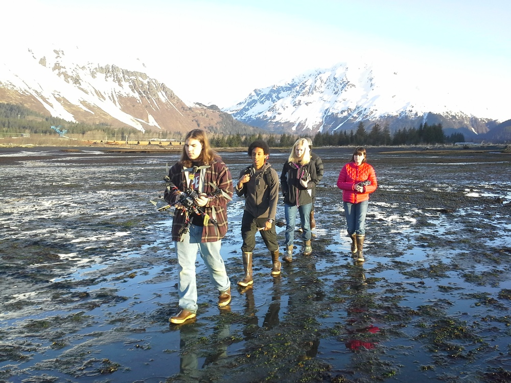 Seward students carry equipment to the tidal flat at the mouth of the Resurrection River.