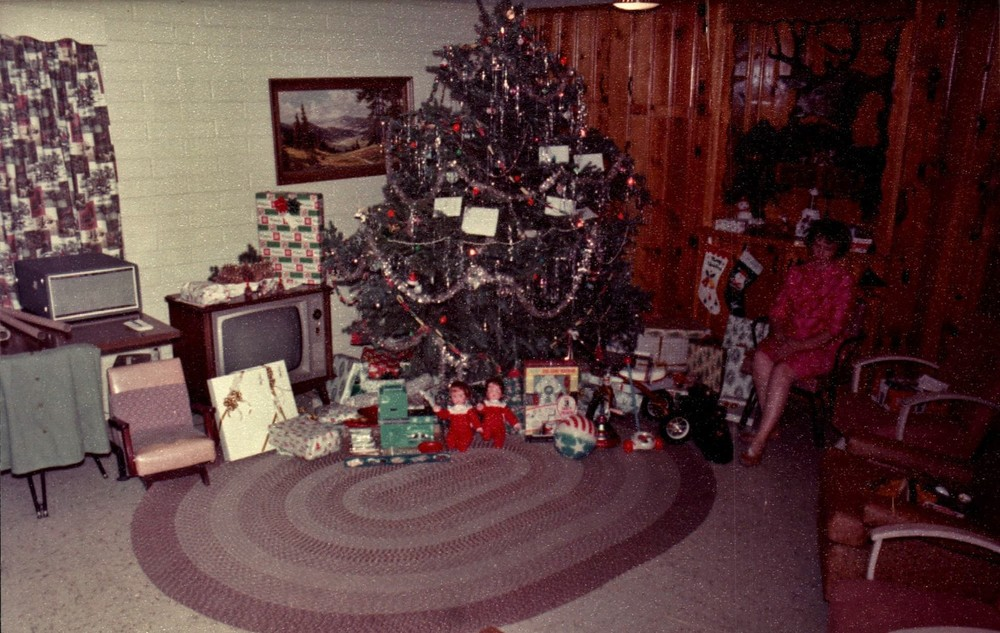 Grandma Palmer sitting with the Christmas tree and all the gifts from Santa.