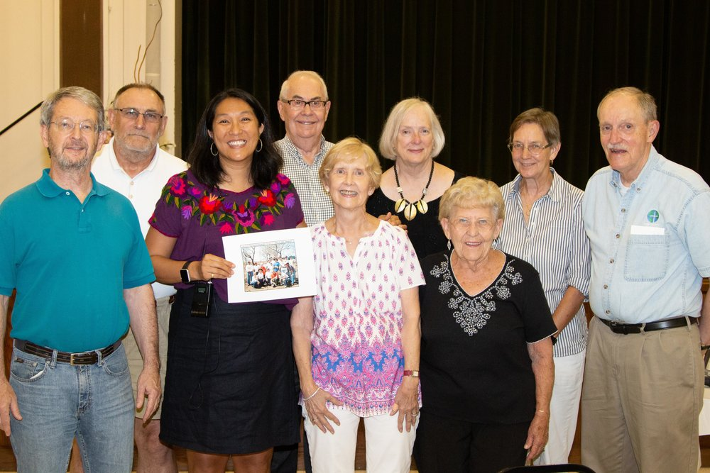Dr. Laura Parajon holding a 2008 group picture alongside those FBC members at a  presentation in 2018 .