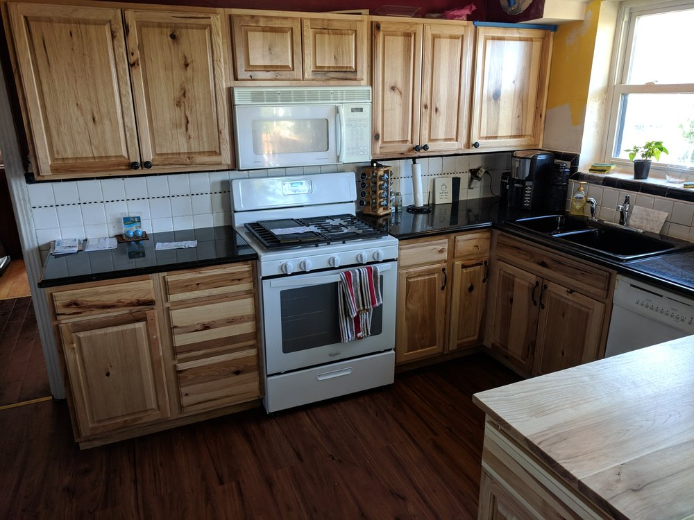 Kitchen remodel in this South City home including cabinet and appliance install, flooring, tile backsplash, and a custom island with slide out drawer and trash pull-out