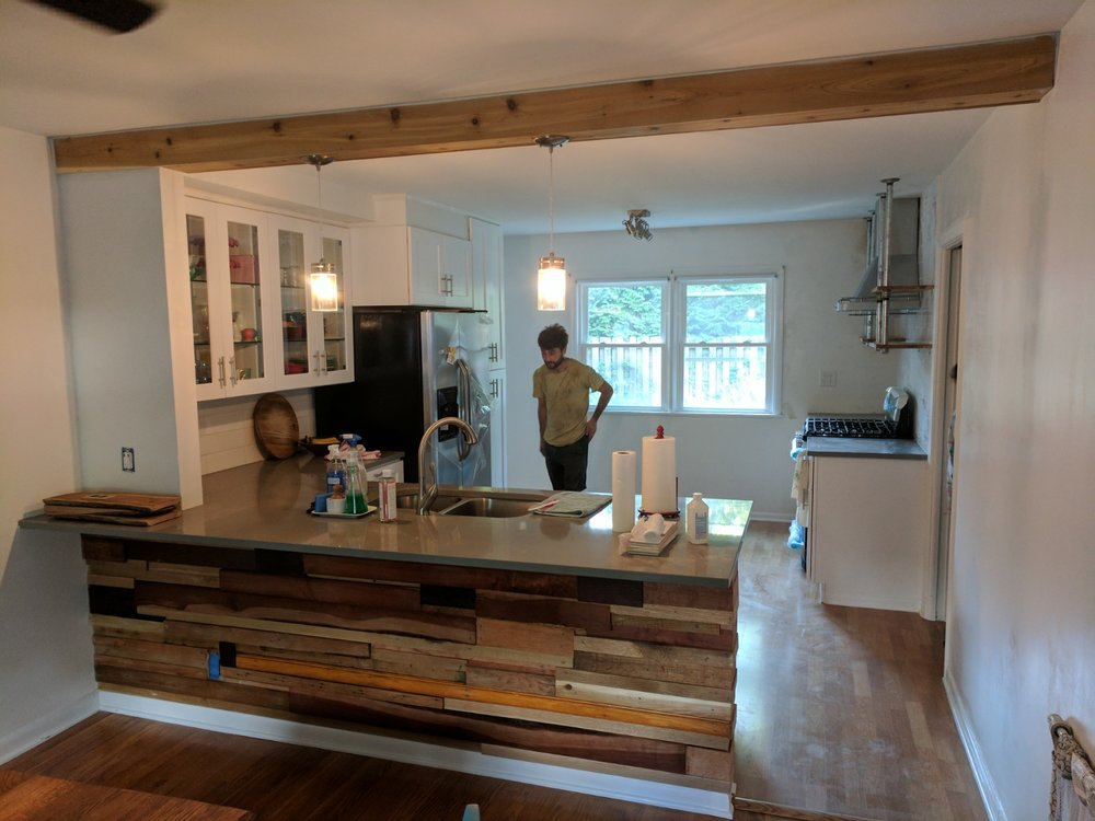 Kitchen remodel in this Webster Groves home. We demolished the wall in between the kitchen and living room and created a half wall breakfast bar with a reclaimed wood treatment, installed cabinets and appliances, and custom shelving.