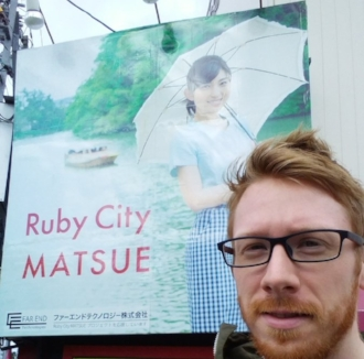 "The Photogenic Zachary Scott and a billboard for ""Ruby City Matsue"" in Shimane Prefecture, Japan"