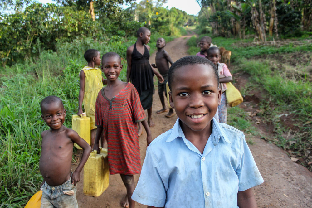 Goretti and her neighbours smile for the camera as they go out to collect water from their local well. The children - boys and girls - keep their hair cut short to stop worms, ticks and lice.
