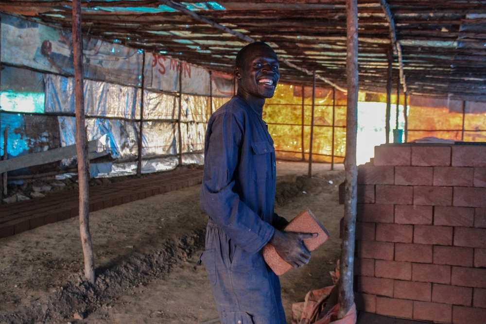 Onyera is piling the new bricks for drying out.