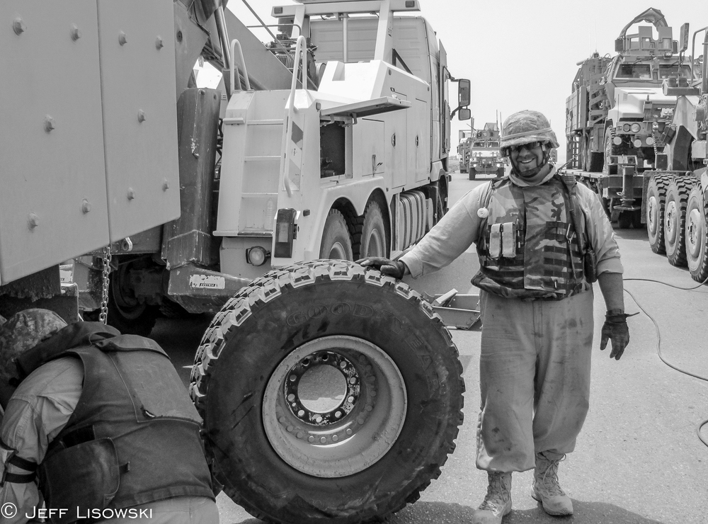 Ken Brower holding an MRAP spare tire- we kept one chained on the HET trailer deck just in case. The summer months meant flat tires for MRAPs on Tampa. All the money and technology into the equipment, but no place for a spare tire. Good job engineers.