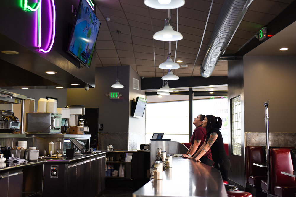 8 p.m.: Myrissa Adams, left, and Holliday watch one of two large TVs above the bar.