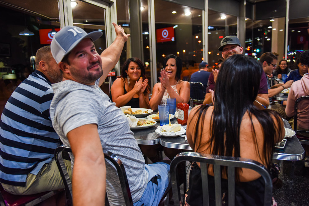 """Midnight: A patron celebrates his birthday with a piece of pie and an improvised French fry candle, while his table and a waitress sing """"Happy Birthday."""""""