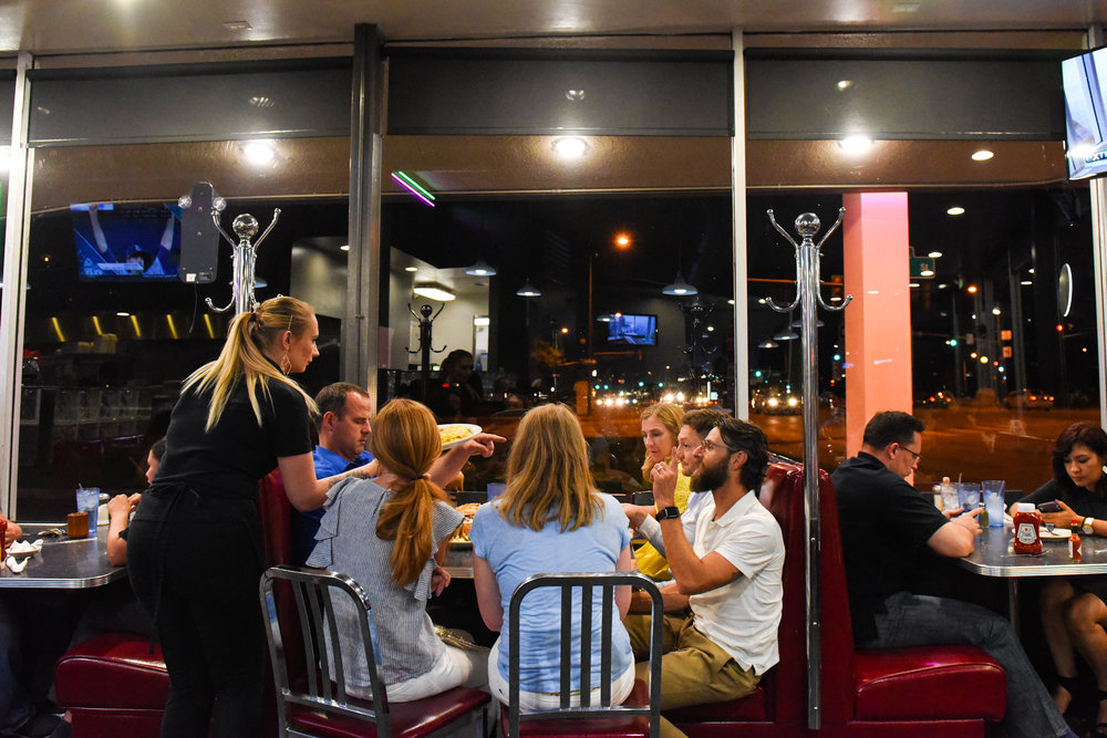 A Denver Diner waitress brings food to a full table. The women at the end of the table pulled up chairs after being dropped off by a pedicab with glowing wheels.