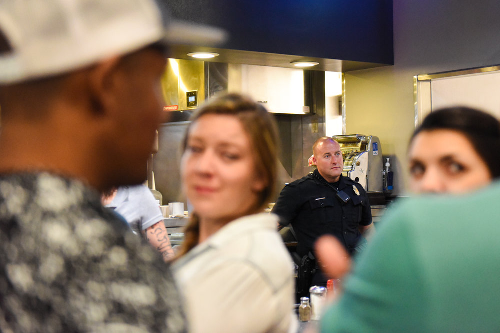 Officer Adam Foisy stands behind the counter at the Denver Diner. Every weekend, a police officer comes to the diner after midnight.