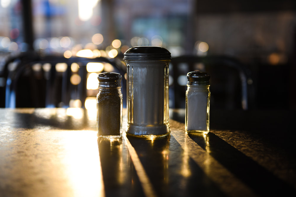 Sunlight shines through salt and pepper shakers on empty tables.