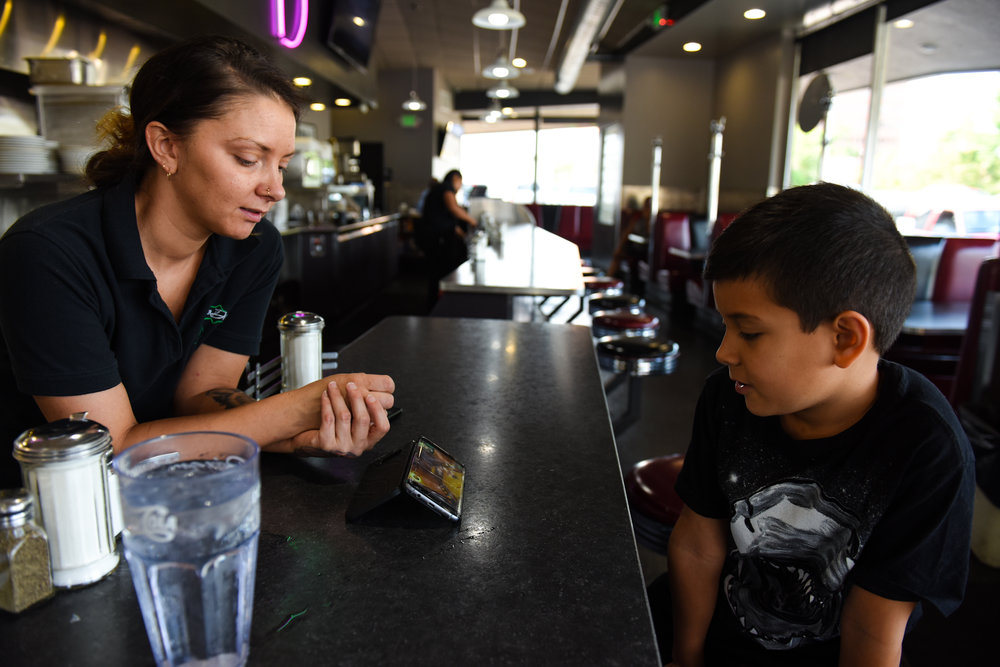 8 a.m: Brittany Graham checks on her son, nine-year-old Gabriel, while he watches a game on YouTube. Brittany has worked at the diner for five years.