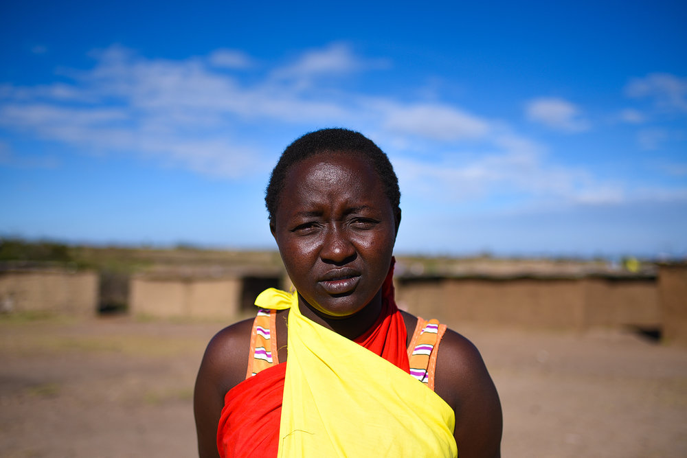 A Maasai woman, Lily, stands in the middle of a group of houses. Women construct the homes.