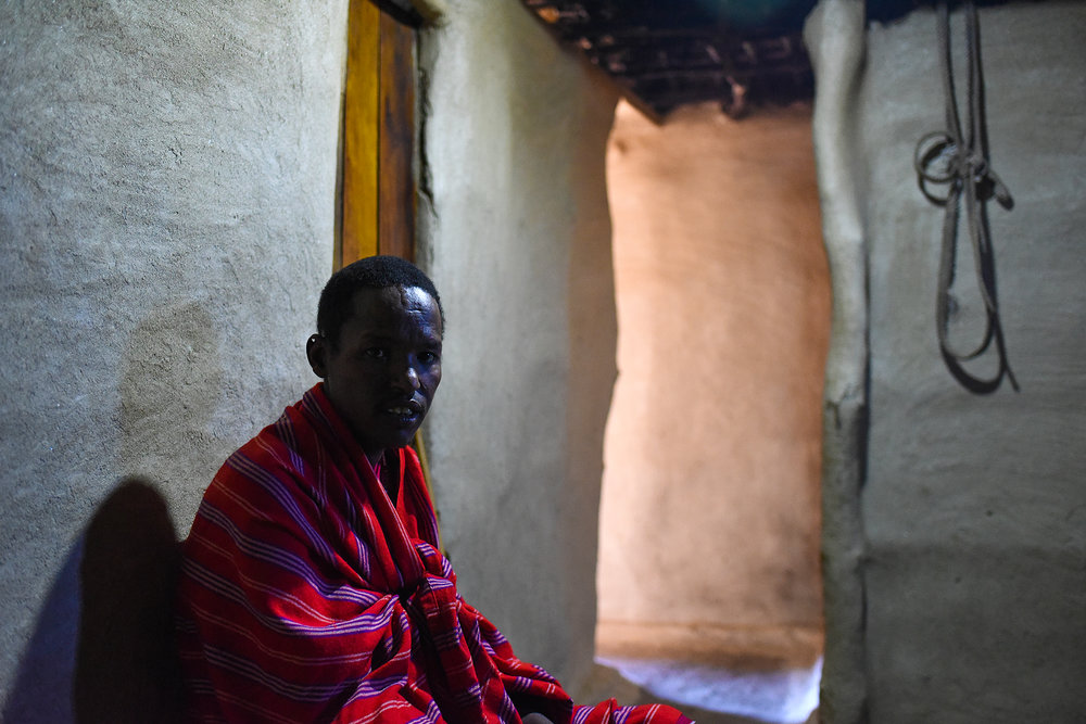 John sits inside his house. Homes are made of timber poles that are plastered by cow dung.