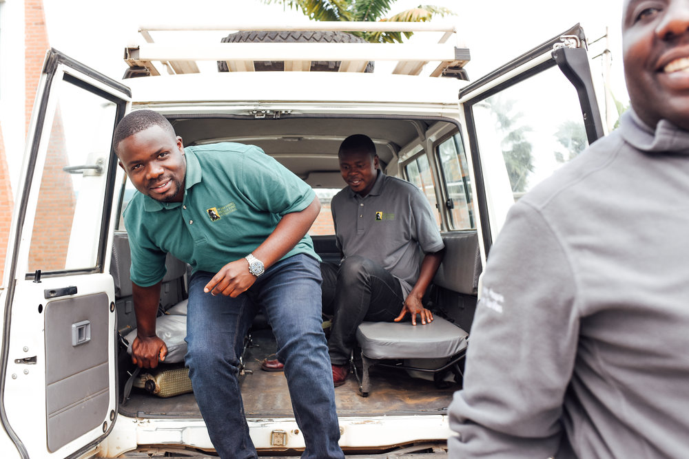 Maurice Ngiramahoro (back), Jean Paul Hirwa; (middle) and Deo Tuyisingize get out of a Fossey Fund field car.