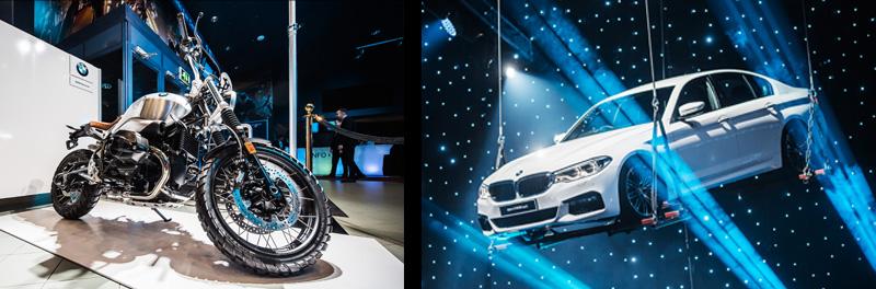 BMW:n moottoripyörä koristaa aulaa vieraiden saapuessa sisään. Oikealla BMW:n auto nostettuna kattoon illallispöytien ylle.
