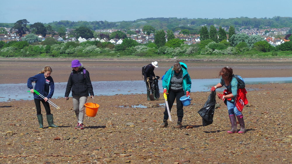 Volunteers enjoy the sunshine whilst cleaning the Estuary